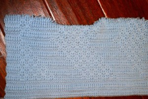 Blanket knitted with borders of 2 black rows alternating with 2 white rows.